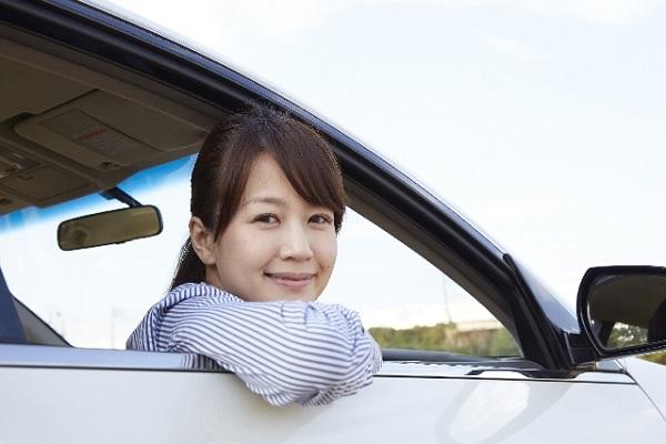 自動車の窓から顔を出す女性